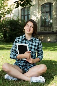 Garota de escola secundária segurando o tablet nas mãos