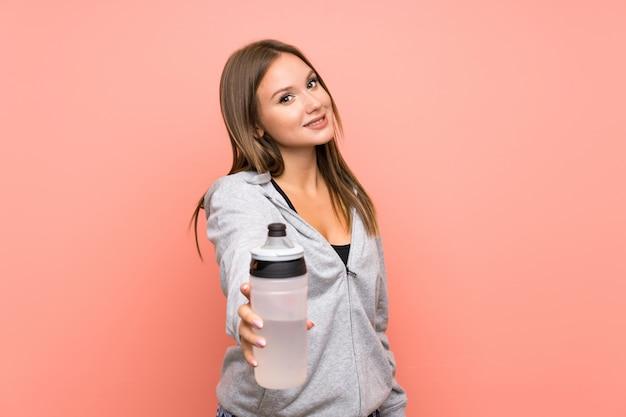 Garota de esporte adolescente com uma garrafa de água sobre o fundo rosa isolado
