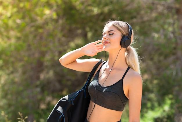 Garota de esporte adolescente fazendo esporte ao ar livre, ouvindo música com fones de ouvido