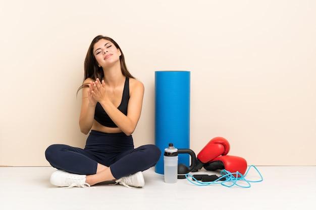 Garota de esporte adolescente sentada no chão aplaudindo após apresentação em uma conferência