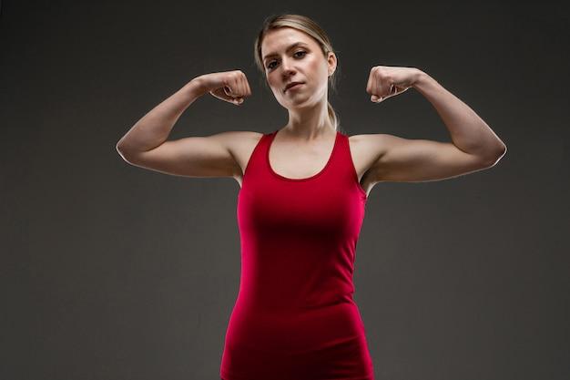 Garota de esportes com músculos em uma parede escura