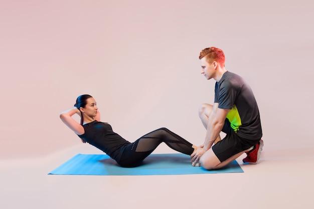 Garota de esportes e cara fazendo exercícios. ele ajuda a garota a agitar a imprensa.