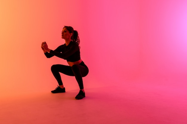 Garota de esportes em um fundo de cor brilhante faz exercícios.