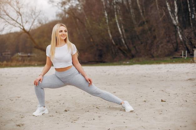 Garota de esportes em um parque de verão de manhã