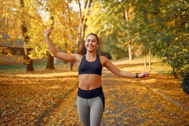 Garota de esportes em um treinamento top preto em um parque de outono