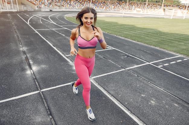 Garota de esportes em um uniforme rosa é executado no estádio