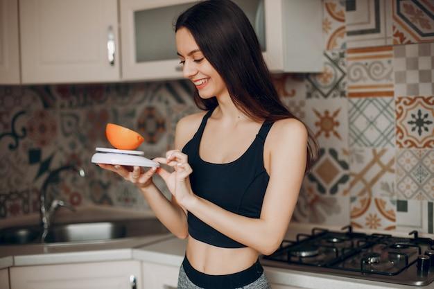 Garota de esportes em uma cozinha com frutas