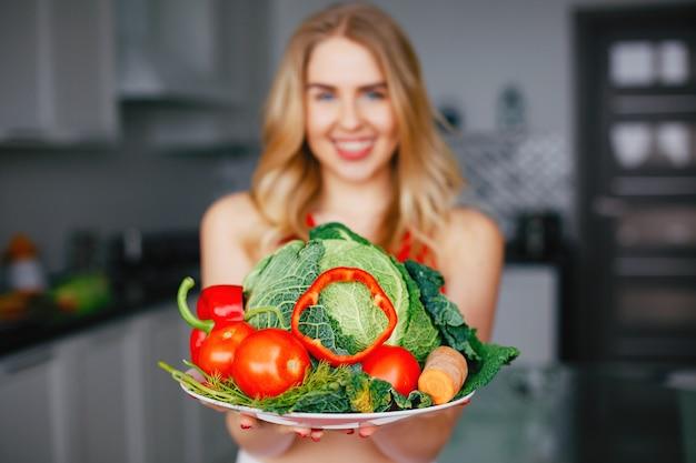 Garota de esportes em uma cozinha com legumes