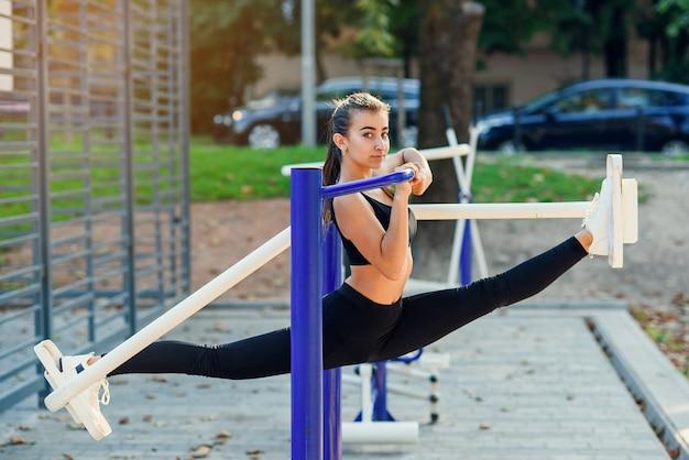Garota de esportes faz barbante no simulador ao ar livre. mulher atlética fazer alongamento ao ar livre antes de treino numa manhã quente de verão.