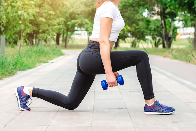 Garota de esportes fazendo exercícios com halteres no parque.