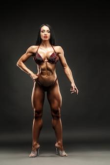 Garota de esportes forte e muscular em posar de biquíni