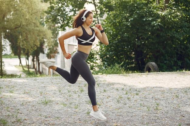 Garota de esportes treinando com fones de ouvido em um parque de verão