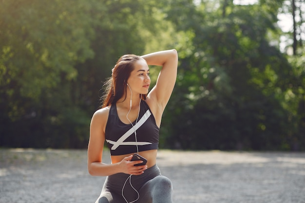 Garota de esportes treinando com telefone e fones de ouvido