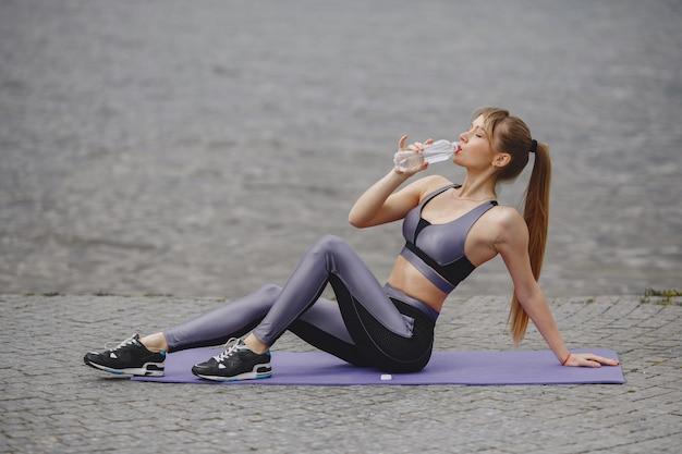 Garota de esportes treinando em um parque de verão