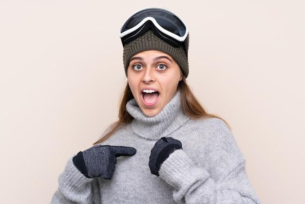 Garota de esquiador adolescente com óculos de snowboard com expressão facial de surpresa