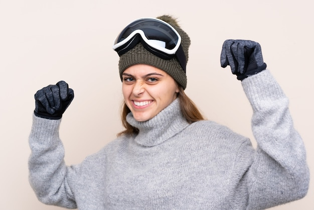 Garota de esquiador adolescente com óculos de snowboard, comemorando uma vitória