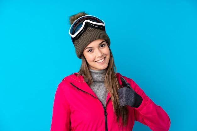 Garota de esquiador adolescente com óculos de snowboard, dando um polegar para cima gesto