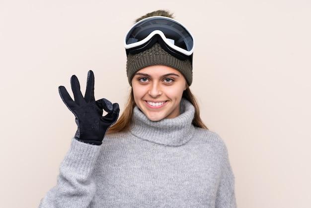 Garota de esquiador adolescente com óculos de snowboard, mostrando sinal de ok com os dedos