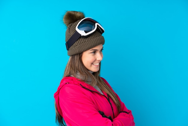 Garota de esquiador adolescente com óculos de snowboard, olhando para o lado
