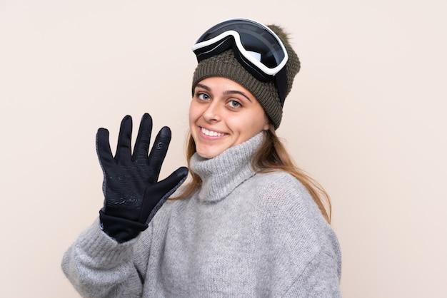 Garota de esquiador adolescente com óculos de snowboard saudando com a mão com expressão feliz