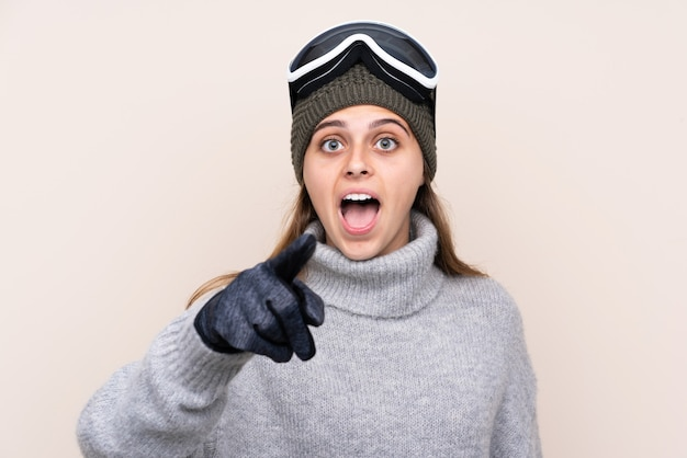 Garota de esquiador adolescente com óculos de snowboard surpreso e apontando a frente