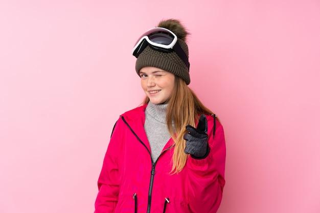 Garota de esquiador adolescente ucraniano com óculos de snowboard sobre dedo isolado pontos-de-rosa para você