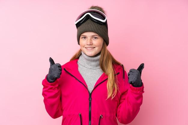 Garota de esquiador adolescente ucraniano com óculos de snowboard sobre fundo rosa isolado, dando um polegar para cima gesto