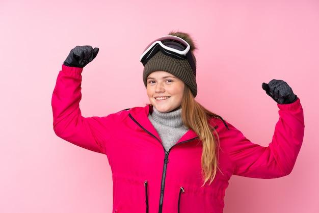 Garota de esquiador adolescente ucraniano com óculos de snowboard sobre rosa isolado comemorando uma vitória
