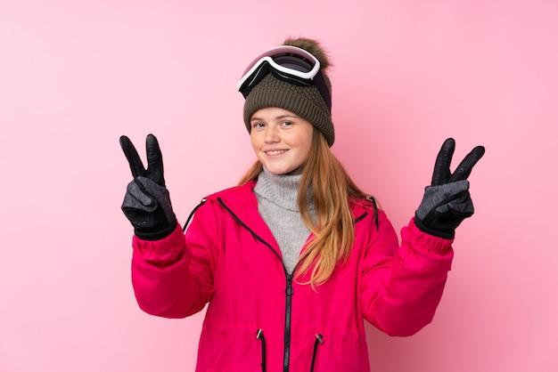 Garota de esquiador adolescente ucraniano com óculos de snowboard sobre rosa isolado sorrindo e mostrando sinal de vitória