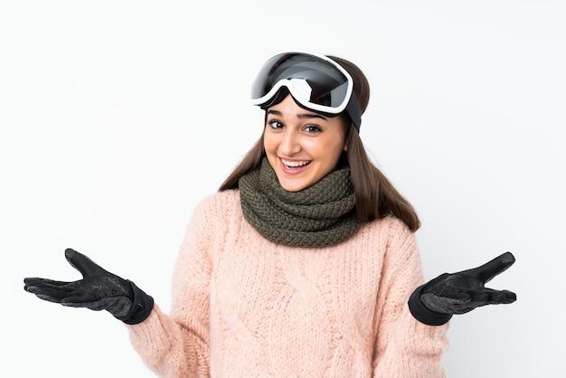 Garota de esquiador com óculos de snowboard com expressão facial chocado