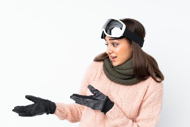 Garota de esquiador com óculos de snowboard sobre parede branca isolada com expressão facial de surpresa