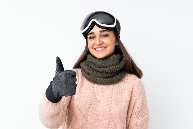 Garota de esquiador com óculos de snowboard sobre parede branca isolada com polegares para cima, porque algo de bom aconteceu