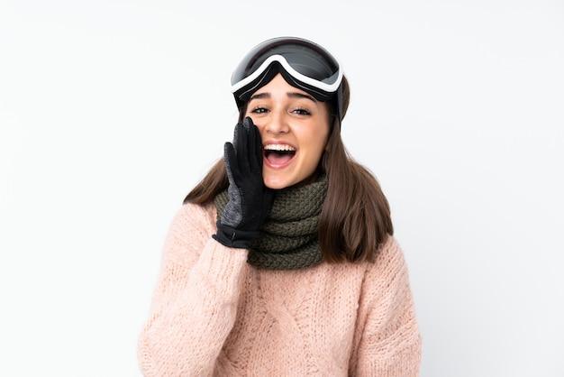 Garota de esquiador com óculos de snowboard sobre parede branca isolada, gritando com a boca aberta