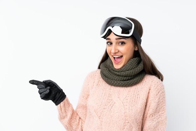 Garota de esquiador com óculos de snowboard sobre parede branca isolada surpreendeu e apontando o dedo para o lado