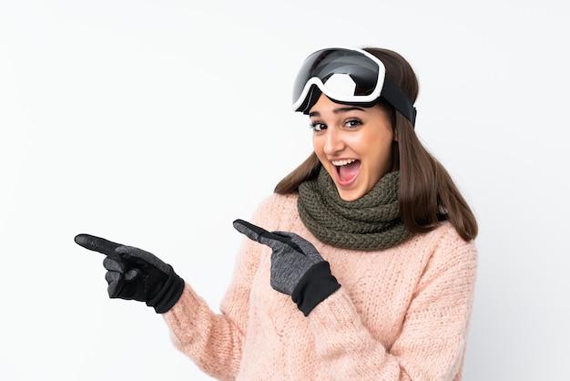 Garota de esquiador com óculos de snowboard sobre parede branca isolada surpreendeu e apontando o lado