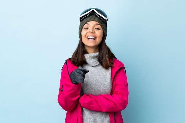 Garota de esquiador de raça mista com óculos de snowboard no azul isolado surpreso e apontando a frente