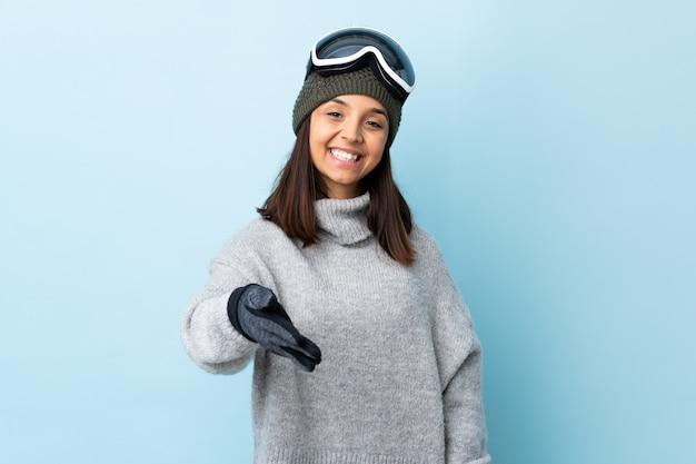 Garota de esquiador de raça mista com óculos de snowboard sobre azul isolado, apertando as mãos para fechar um bom negócio