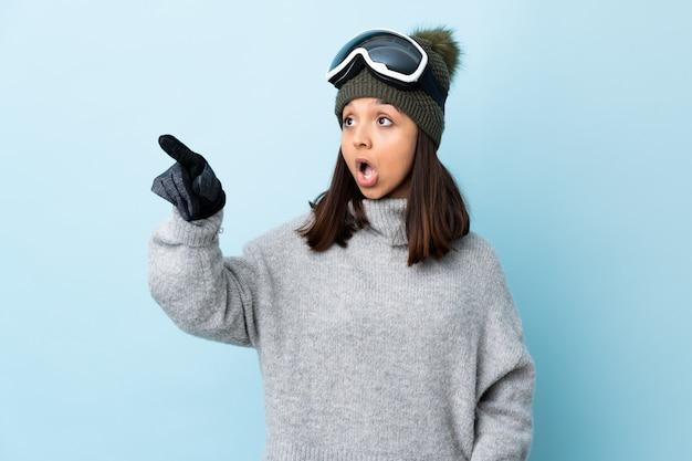 Garota de esquiador de raça mista com óculos de snowboard sobre parede azul apontando para fora