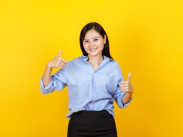 Garota de estilo japonês bonito e jovem em pé e levantar a mão mostra os polegares com rosto de sorriso no fundo amarelo.