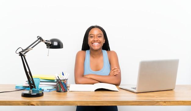 Garota de estudante adolescente afro-americana com cabelo longo trançado no seu local de trabalho, mantendo os braços cruzados em posição frontal