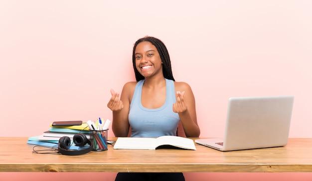 Garota de estudante adolescente americano africano com cabelo longo trançado em seu local de trabalho, fazendo gesto de dinheiro