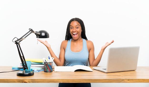 Garota de estudante adolescente americano africano com cabelo longo trançado no seu local de trabalho com expressão facial chocado
