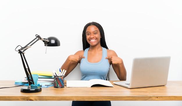 Garota de estudante adolescente americano africano com cabelo longo trançado no seu local de trabalho com expressão facial de surpresa