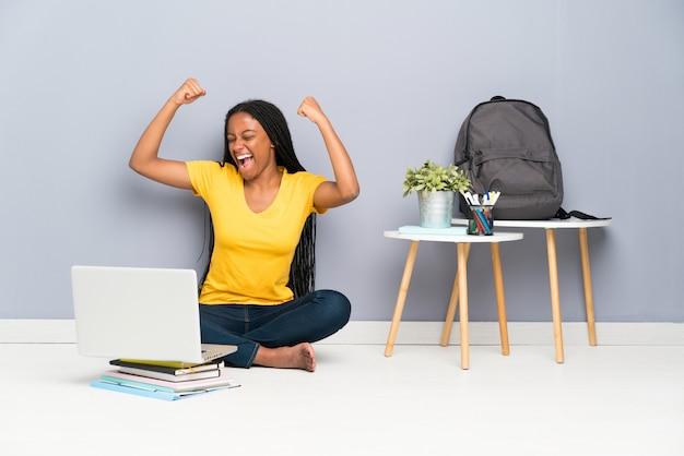 Garota de estudante adolescente americano africano com cabelo longo trançado, sentado no chão comemorando uma vitória