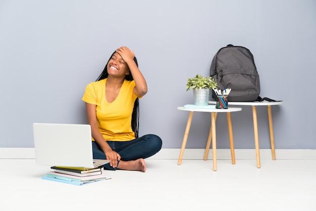Garota de estudante adolescente americano africano com cabelo longo trançado sentado no chão rindo