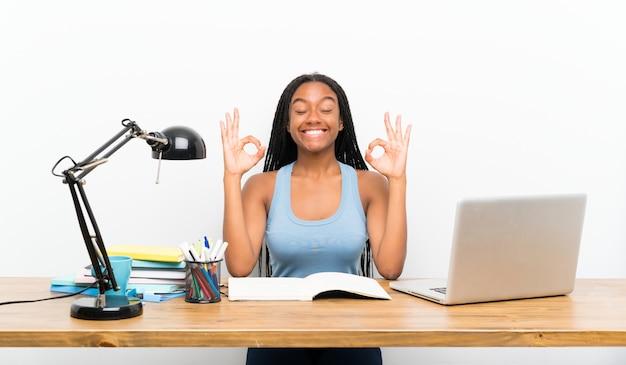 Garota de estudante adolescente americano africano com longos cabelos trançados em seu local de trabalho em pose de zen