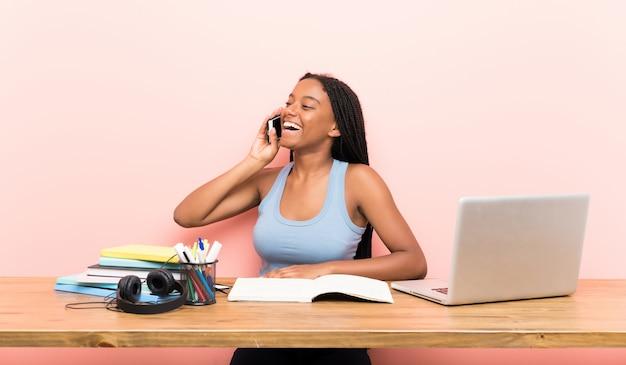 Garota de estudante adolescente americano africano com longos cabelos trançados em seu local de trabalho, mantendo uma conversa