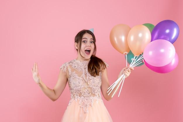 Garota de festa eufórica de frente com boné segurando balões e abrindo as mãos