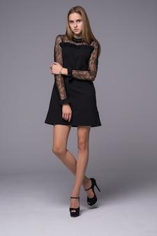 Garota de figura fina, vestida com vestido de seda preto com renda