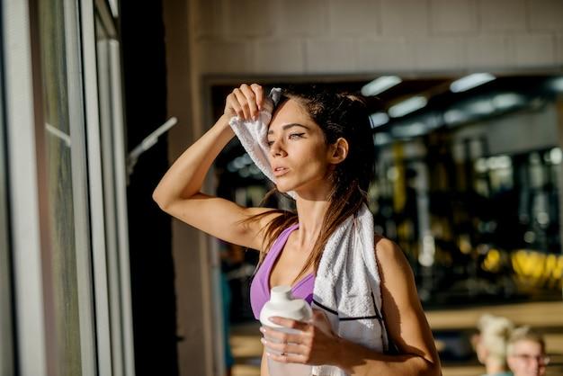 Garota de fitness de forma atraente cansada, enxugando o suor com uma toalha no ginásio perto da janela.